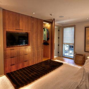 Modelo de dormitorio principal, contemporáneo, de tamaño medio, sin chimenea, con paredes beige, suelo de madera en tonos medios y suelo marrón