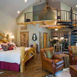 Photo of a mid-sized traditional loft-style bedroom in Little Rock with beige walls, medium hardwood floors, no fireplace and brown floor.