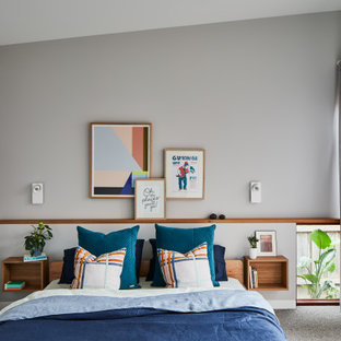 Contemporary bedroom in Melbourne with grey walls, carpet, grey floor and vaulted.