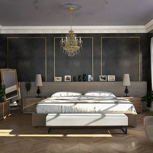 Idee per una camera degli ospiti moderna di medie dimensioni con pareti nere, pavimento in laminato, camino ad angolo, cornice del camino in metallo e pavimento marrone