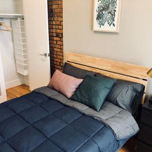 Imagen de habitación de invitados de tamaño medio, sin chimenea, con paredes beige, suelo de madera clara, marco de chimenea de ladrillo y suelo beige