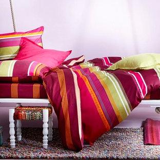 На фото: гостевая спальня среднего размера в стиле современная классика с фиолетовыми стенами, полом из ламината и розовым полом без камина с