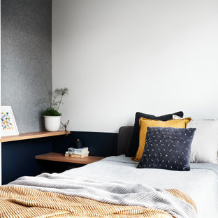 Mid-sized scandinavian bedroom in Sydney with white walls, carpet and grey floor.