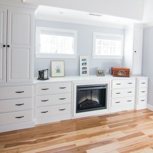 Example of a large transitional master light wood floor bedroom design in Boston with blue walls, a standard fireplace and a wood fireplace surround