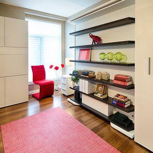 Imagen de habitación de invitados minimalista, pequeña, sin chimenea, con paredes beige y suelo de madera en tonos medios