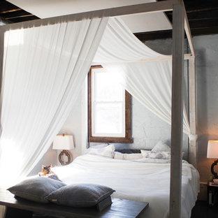 Ejemplo de dormitorio tipo loft, moderno, de tamaño medio, con paredes grises, suelo de madera en tonos medios, estufa de leña, marco de chimenea de ladrillo y suelo gris