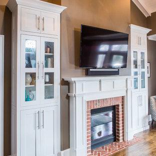 Modelo de dormitorio principal, tradicional, grande, con paredes marrones, suelo de madera en tonos medios, chimenea tradicional y marco de chimenea de ladrillo