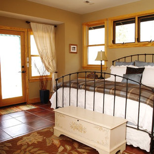 Inspiration for a mid-sized country guest bedroom in Other with beige walls, terra-cotta floors, no fireplace and red floor.