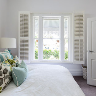 Inspiration for a mid-sized traditional master bedroom in Melbourne with white walls, carpet, a standard fireplace, a plaster fireplace surround and grey floor.