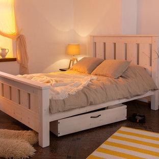 Imagen de dormitorio nórdico, grande, con paredes blancas, chimenea de doble cara y marco de chimenea de piedra