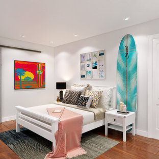 Inspiration for a beach style medium tone wood floor and brown floor bedroom remodel in San Diego with white walls