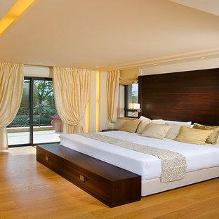 Modern inredning av ett sovrum, med vita väggar, mellanmörkt trägolv och gult golv