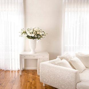 Ispirazione per una camera da letto eclettica con pareti beige e pavimento in legno massello medio