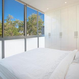 Ejemplo de dormitorio minimalista con paredes blancas