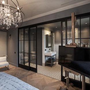 Imagen de dormitorio principal, urbano, grande, con paredes grises y suelo de madera en tonos medios