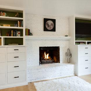 Diseño de dormitorio principal, ecléctico, de tamaño medio, con paredes blancas, suelo de madera clara, chimenea tradicional y marco de chimenea de ladrillo