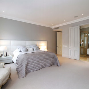 Photo of a large contemporary master bedroom in London with grey walls, carpet and no fireplace.