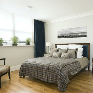 Photo of a contemporary bedroom in London with grey walls and light hardwood flooring.