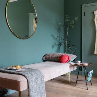 Scandi bedroom in London with green walls, light hardwood flooring and beige floors.