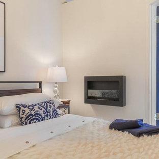 Esempio di una piccola camera matrimoniale contemporanea con pavimento in legno massello medio e camino sospeso