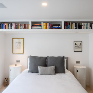 Photo of a small contemporary bedroom in London with white walls, light hardwood flooring and beige floors.