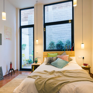 Design ideas for a small modern loft-style bedroom in Barcelona with white walls, terra-cotta floors and no fireplace.