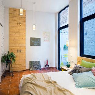 Modelo de dormitorio tipo loft, moderno, pequeño, sin chimenea, con paredes blancas y suelo de baldosas de terracota