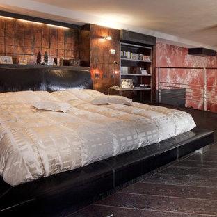 Photo of a large industrial loft-style bedroom in Milan with dark hardwood floors.