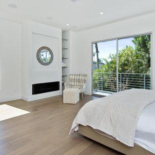 На фото: хозяйская спальня среднего размера в стиле ретро с белыми стенами, светлым паркетным полом, горизонтальным камином и фасадом камина из штукатурки с