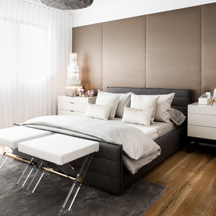 This is an example of a mid-sized contemporary master bedroom in Melbourne with white walls, medium hardwood floors, no fireplace and brown floor.