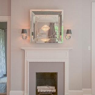 Ejemplo de dormitorio principal, contemporáneo, grande, con paredes púrpuras, suelo de madera en tonos medios, chimenea tradicional y marco de chimenea de yeso