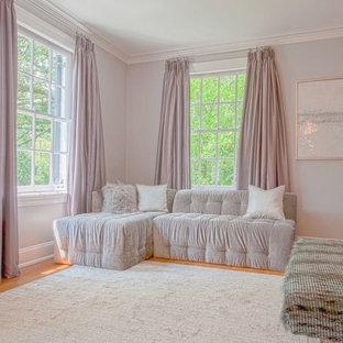 Diseño de dormitorio principal, actual, grande, con paredes púrpuras, suelo de madera en tonos medios, chimenea tradicional y marco de chimenea de yeso