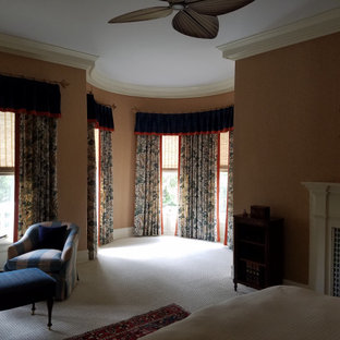 This is an example of a large traditional master bedroom in Other with brown walls, carpet, a standard fireplace, a tile fireplace surround and beige floor.