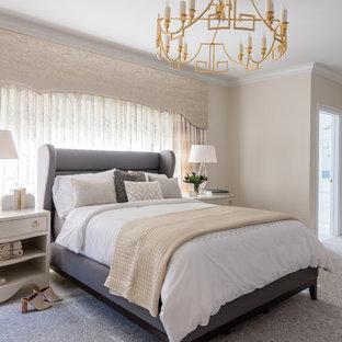 Immagine di una grande camera matrimoniale tradizionale con pareti beige, moquette, pavimento grigio, camino classico e cornice del camino piastrellata