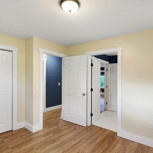 他の地域の中サイズのコンテンポラリースタイルのおしゃれな客用寝室 (黄色い壁、無垢フローリング、茶色い床) のインテリア
