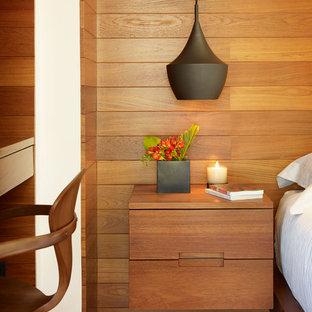 Diseño de dormitorio principal, exótico, de tamaño medio, con paredes marrones, suelo de madera oscura y suelo marrón