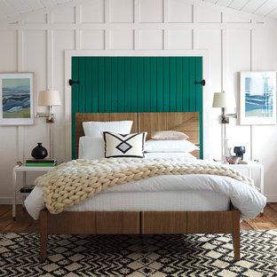 Ejemplo de dormitorio costero, de tamaño medio, sin chimenea, con paredes blancas y suelo de madera en tonos medios