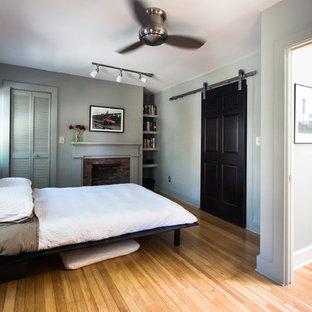 Неиссякаемый источник вдохновения для домашнего уюта: спальня в стиле современная классика с серыми стенами, паркетным полом среднего тона, стандартным камином и фасадом камина из кирпича