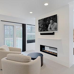 Ejemplo de dormitorio principal, contemporáneo, grande, con paredes blancas, moqueta, chimenea de doble cara, marco de chimenea de yeso y suelo beige