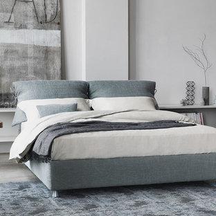 Modelo de dormitorio tipo loft, minimalista, de tamaño medio, sin chimenea, con paredes grises y suelo de cemento