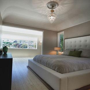Modelo de dormitorio principal, clásico renovado, de tamaño medio, sin chimenea, con paredes beige y suelo de bambú