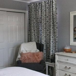 シカゴのカントリー風おしゃれな主寝室 (グレーの壁、無垢フローリング、木材の暖炉まわり)