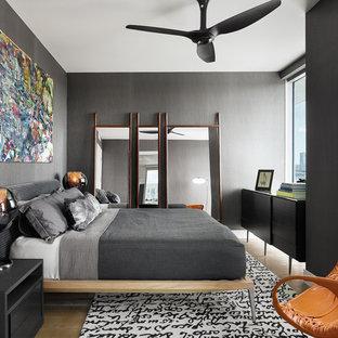 Diseño de dormitorio actual, de tamaño medio, sin chimenea, con paredes grises y suelo de madera clara