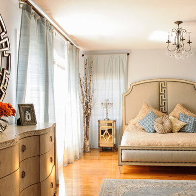 Mid-sized elegant master medium tone wood floor bedroom photo in New York with gray walls and no fireplace