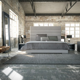 Photo of a large industrial loft-style bedroom in Los Angeles with grey walls and no fireplace.