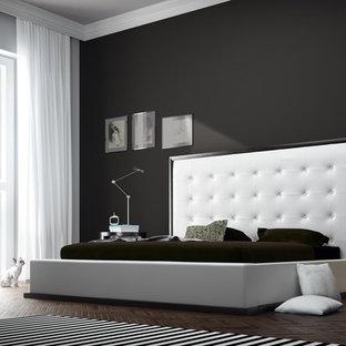 Immagine di una grande camera matrimoniale moderna con pareti nere, parquet scuro e nessun camino