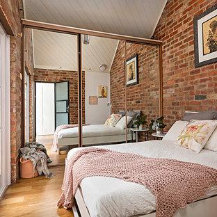 Ejemplo de dormitorio principal, minimalista, de tamaño medio, sin chimenea, con paredes rojas, suelo de madera en tonos medios y suelo marrón