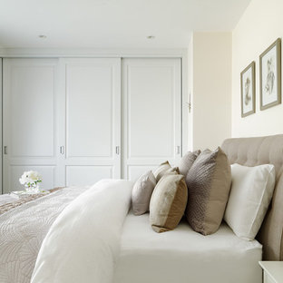 Medium sized traditional master bedroom in Kent with beige walls, carpet and grey floors.