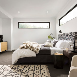 Photo of a contemporary master bedroom in Melbourne with white walls, carpet and brown floor.