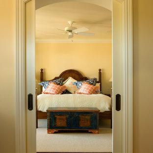 Imagen de dormitorio principal, tradicional, de tamaño medio, sin chimenea, con paredes amarillas y suelo de madera en tonos medios